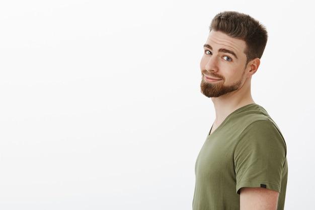 Inquadratura del primo piano dell'affascinante ragazzo barbuto carismatico in t-shirt in piedi di profilo girando la testa e sorridendo felice e spensierato in posa felice contro il muro bianco