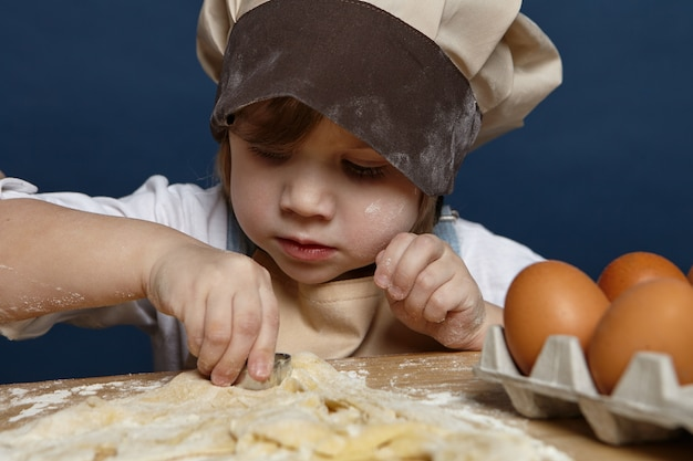Close up shot of charming cute little girl wearing big chef cap making cookies at the kitchen table, using bakery moulds, having focused concentrated expression. children, cooking and baking concept