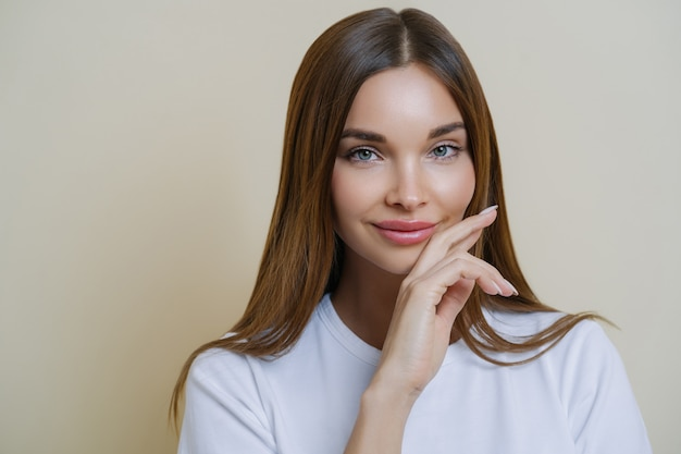 Close up shot of charming dark haired woman keeps hand on cheek, dressed in casual white t shirt