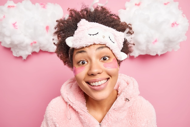 Close up shot of charming smiling woman looks directly at camera applies collagen pads under eyes wears sleepmask nightwear expresses positive emotions isolated on pink wall