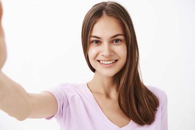 Primo piano sparato di affascinante giovane bruna femmina europea felice con capelli lunghi e forti e pulire sking sorridente amichevole mentre si tira la mano in avanti come se si stesse prendendo selfie