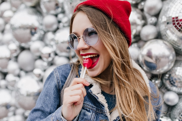 Close-up shot of charming young woman having fun during photoshoot with red candy. attractive girl in denim jacket licking lollipop on sparkle wall.