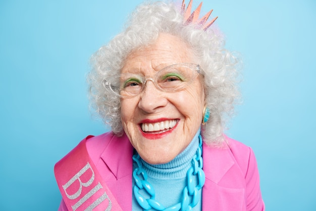 Close up shot of cheerful elderly birthday woman looks happily, wears princess crown spectacles stylish clothes celebrates her 80th birthday