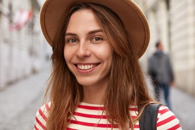 Immagine ravvicinata di allegro avventuriero femminile indossa copricapo, maglione a righe, ha un'espressione felice, passeggia all'aperto nello spazio promozionale della città