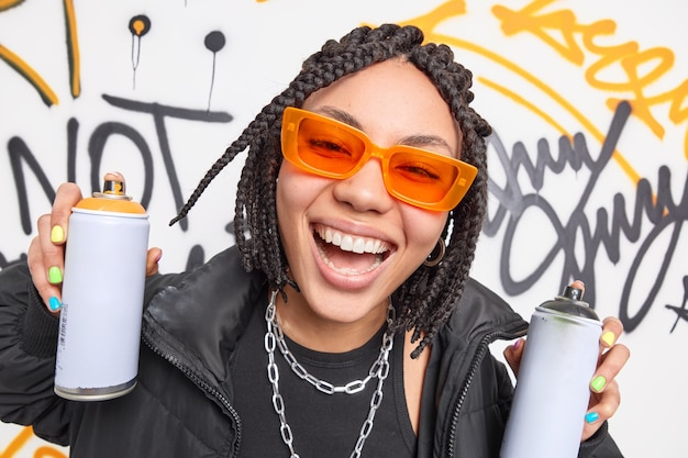 Close up shot of cheerful teenage girl smiles broadly has fun holds two aerosol sprays for drawing graffiti spends free time in urban place wears trendy orange sunglasses and black fashionable jacket