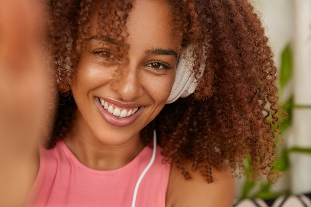 Close up shot of cheerful woman has crisp hair, toothy smile, enjoys recreation time, feels amused, listens favourite music in headphones, makes selfie portrait, models indoor