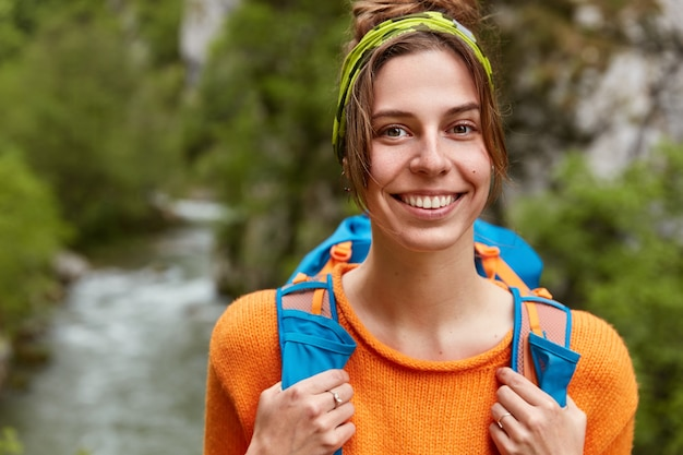 Close up shot of cheerful woman tourist, dressed in orange jumper, strolls near small stream in green forest