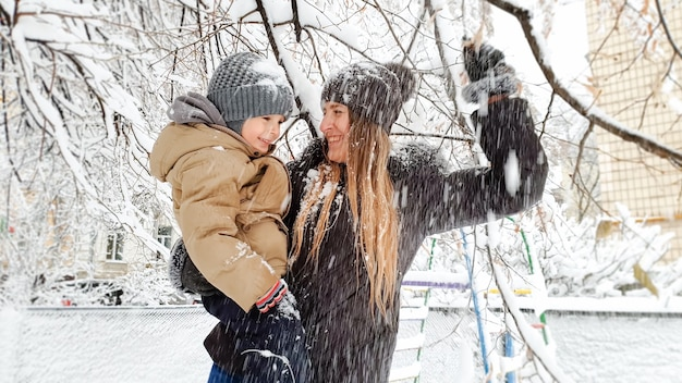 Close up shot of cheerful young mother with her pretty son in jacket and hat playing with snow covered tree on the playground in the park