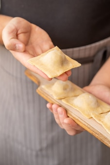 Close-up shot chef holding in hand filled pasta