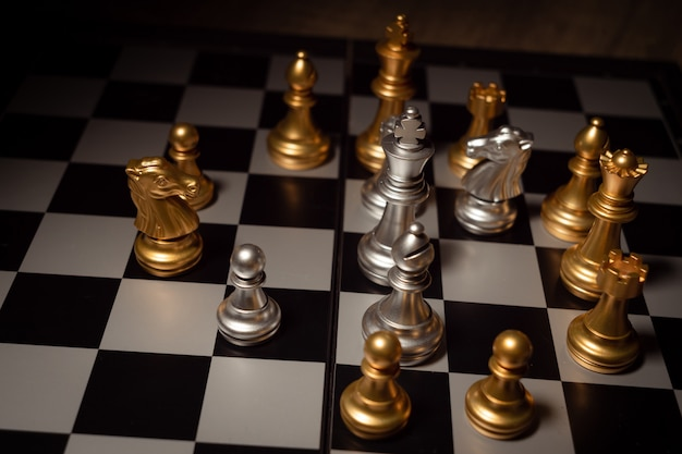 Close up shot chess on the board game with dark mood and tone process competition concept