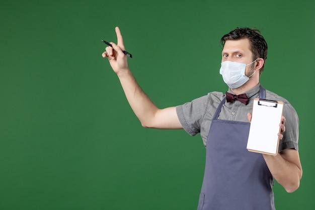 Immagine ravvicinata del cameriere maschio interessato in uniforme con maschera medica e tenendo la penna del libro degli ordini rivolta verso l'alto su sfondo verde