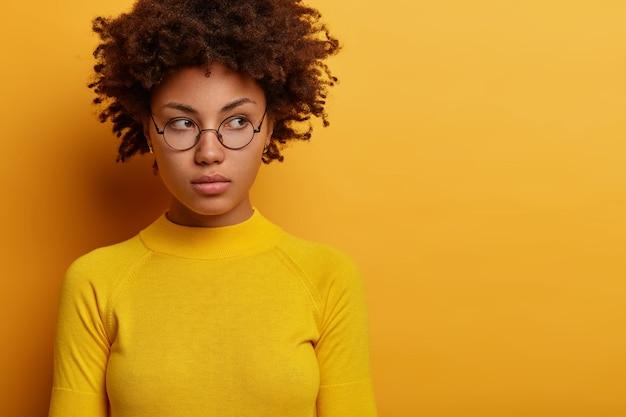 Immagine ravvicinata di giovane modello femminile contemplativo indossa occhiali rotondi e vestiti gialli, guarda da parte con espressione pensierosa, pensa al piano, posa al coperto, spazio vuoto per la tua pubblicità