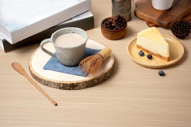 コーヒーショップのカフェでテーブルの本と一緒にコーヒーとケーキのショットのカップを閉じます