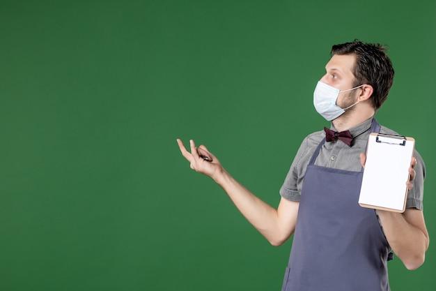Immagine ravvicinata di curioso cameriere maschio in uniforme con maschera medica e tenendo la penna del libro degli ordini su sfondo verde