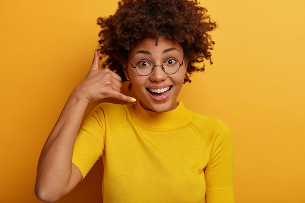 Close up shot of curly beautiful african american woman makes phone gesture, says call me back, wears round glasses and casual t shirt, poses against yellow  wall. communication sign