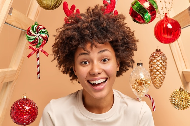 Close up shot of curly haired woman smiles broadly has white teeth and healthy dark skin wears red reindeer antlers looks gladfully at camera expresses happiness surrounded by christmas toys