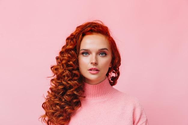 Colpo del primo piano della donna riccia in maglione rosa