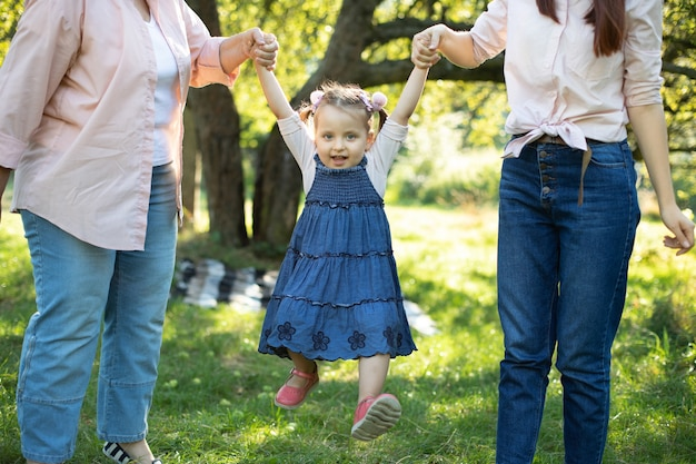 Close up shot of cute pretty little child girl, having fun outdoors and flying in the air while holding hands of her mom and grandma. happy child walking with thei mommy and granny in the park.