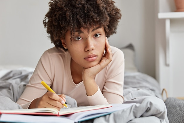 Close up shot of dark skinned girl makes notes of ideas in notebook, lies in bed