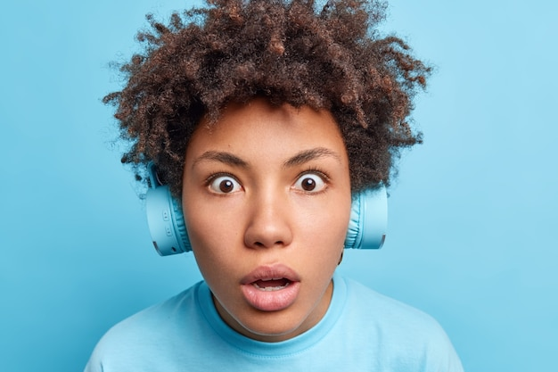 Close up shot of dark skinned girl with afro hair stares bugged eyes has startled expression being shocked by something listens music via wireless headphones isolated over blue wall. omg concept