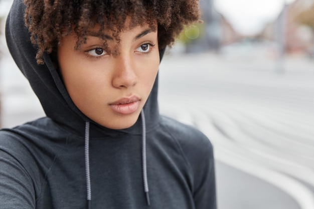 Close up shot of dark skinned hipster has thoughtful expression, wears casual hoodie