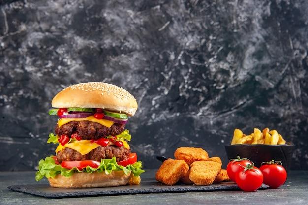 Immagine ravvicinata di deliziosi panini e pepite di pollo ketchup su vassoio nero pomodori su superficie di colore scuro