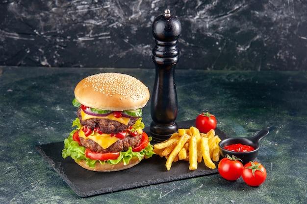 Immagine ravvicinata di un delizioso panino e patatine al pepe su un vassoio di colore scuro pomodori su superficie nera