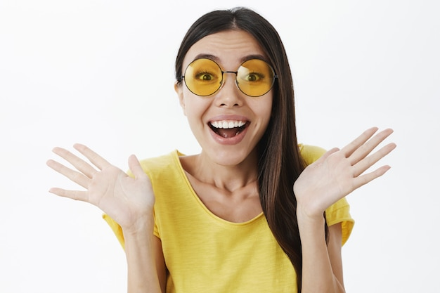 Close-up shot of delighted charming stylish woman in trendy sunglasses and yellow t-shirt waving raised palms near shoulders