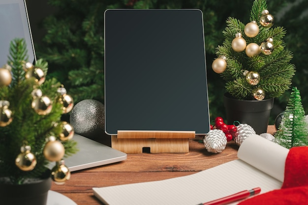 Close up shot of digital device on wooden table with christmas decorations