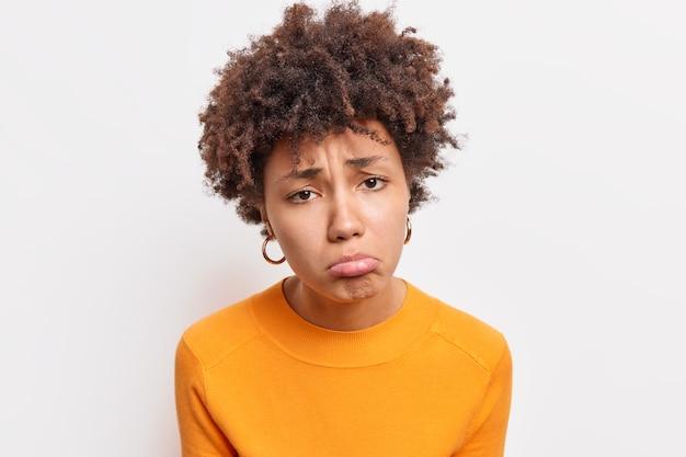 Primo piano di malcontento, triste donna afroamericana, insoddisfatta, offesa da qualcuno vestito con un maglione arancione isolato su un muro bianco, si sente rimpianto e tristezza. emozioni negative