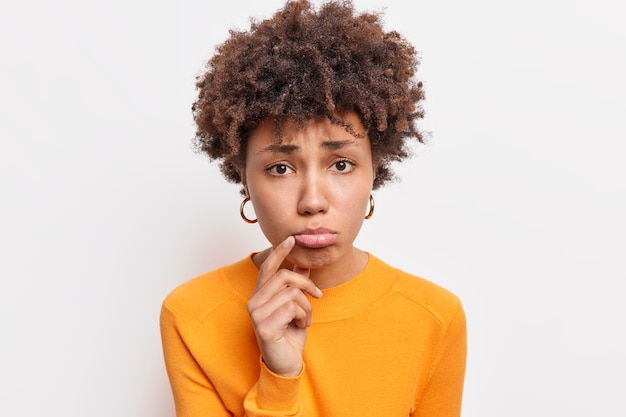 Close up shot of displeased dark skinned woman purses lower lip has upset expression being disappointed or offended wears casual orange jumper isolated over white wall. negative emotions