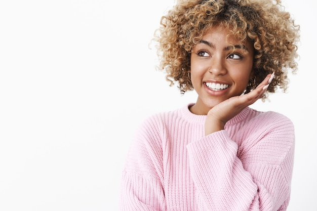 Close-up shot of dreamy tender and cute african-american stylish female in warm winter sweater touching cheek and smiling delighted at upper left corner enjoying perfect skin condition