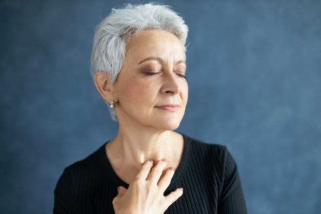 Close up shot of elegant attractive middle aged female with gray hair and wrinkles, closing eyes and smiling, touching neck, applying anti aging cream
