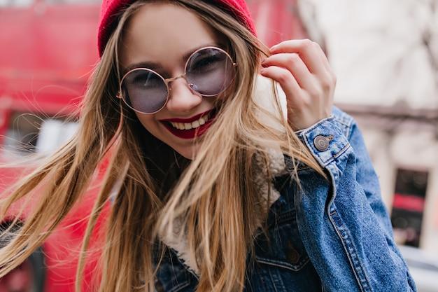 Colpo del primo piano della ragazza elegante con gli occhiali blu che ride mentre ci si rilassa in città. ritratto all'aperto del modello femminile emotivo in giacca di jeans.