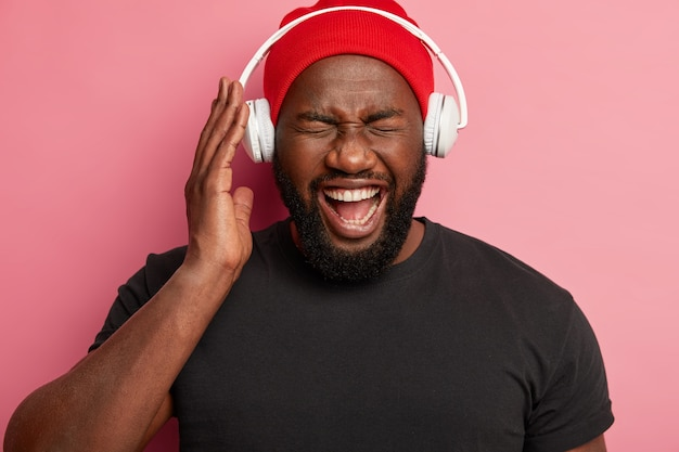 Close up shot of emotional happy dark skinned guy enjoys listening music with high volume in headphones