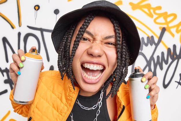 Close up shot of emotional teenage girl exclaims loudly shows white teeth uses aerosol sprays for drawing graffiti wears stylish black hat and orange jacket enjoys spare time