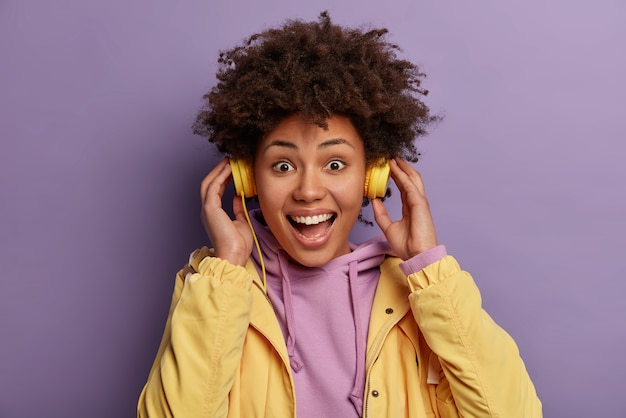 Close up shot of emotive cheerful hipster girl wears headphones, enjoys rhythm of music, listens audio track, has carefree expression