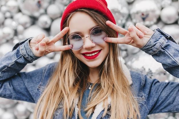 Primo piano sparato di entusiasta ragazza bionda in posa con il segno di pace davanti a palle da discoteca. ritratto di donna europea felice in giacca di jeans che esprime felicità.