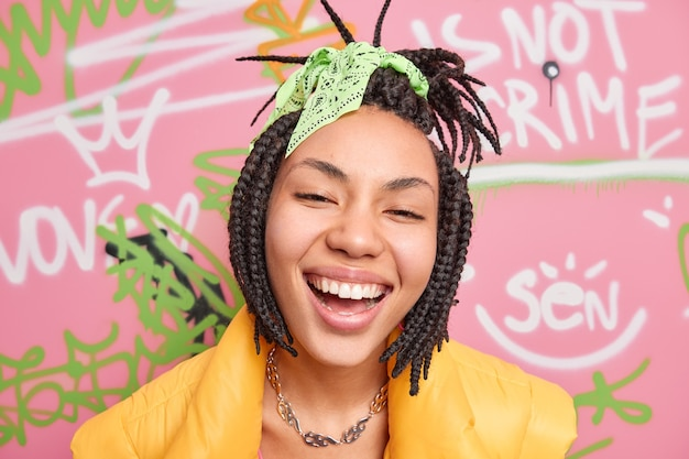 Close up shot of ethnic teenage girl smiles broadly dressed in street style has tendy dreadlocks hairstyle poses against graffiti wall being part of youth gang