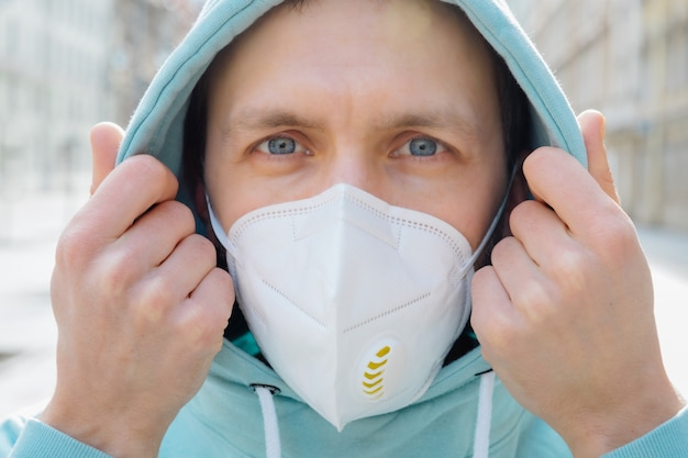 Close up shot of european man protects face with respiratory mask, wears hoodie, poses outdoor on street, looks seriosuly at camera, prevents coronavirus or covid-19, flu. street during quarantine