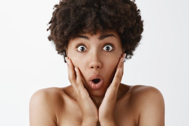 Close-up shot of excited and amazed stunned cute naked african american woman with curly hair loosing speech from astonishing news holding palms on cheeks folding lips and staring impressed