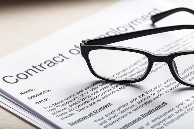 Close up shot of eyeglasses  on contract document papers