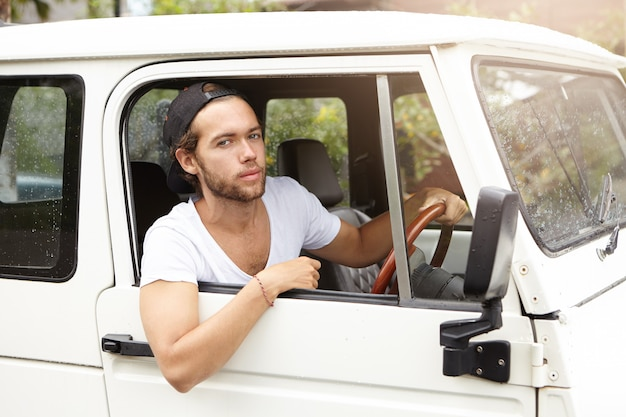 Close up shot of fashionable handsome young bearded model posing inside white jeep on driver's seat holding hand on steering wheel and looking with confident expression on his face