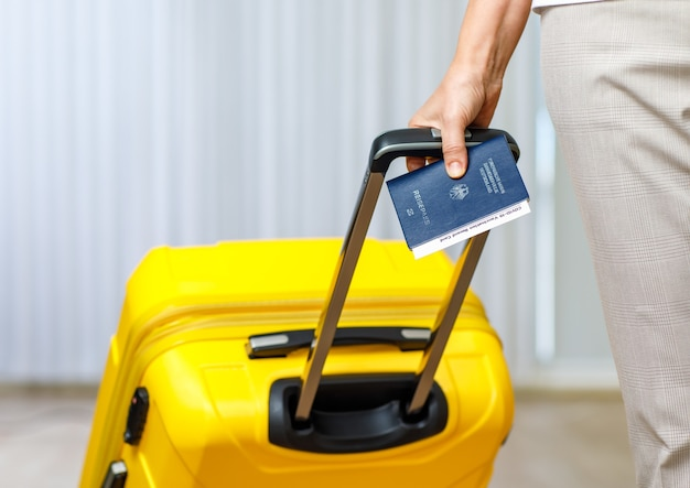 Close up shot of female hand holding deutschland passport coronavirus covid-19 vaccination record card certificate and pull yellow trolley luggage bag to traveling abroad after lockdown quarantine.