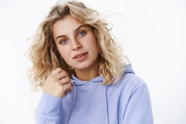 Close-up shot of feminine and gentle young european female with short blond hair and blue eyes tilting head open sensually lips and holding hand near face gazing passionate and flirty at camera