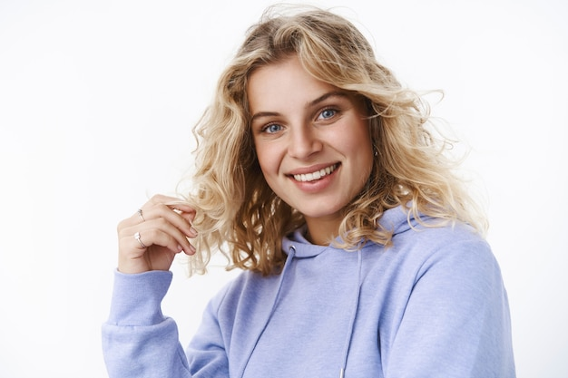 Close-up shot of flirty and feminine adult cute woman in 25s with blue eyes playing with curl and smiling at camera looking with interest and delight as having nice carefree conversation