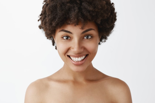 Close-up shot of flirty and feminine confident african american woman with broad bright smile posing naked being satisfied with great skin condition after cosmetological treatment