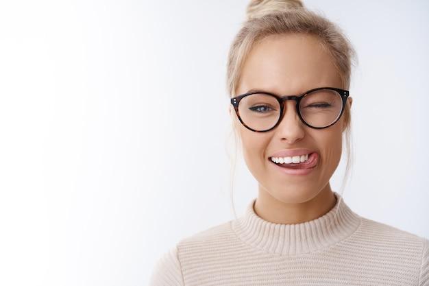 Primo piano di una donna bionda caucasica civettuola e giocosa con gli occhiali, taglio di capelli pettinato, strizzando l'occhio felicemente con un atteggiamento positivo che mostra la lingua che si gode i fine settimana su sfondo bianco