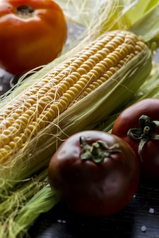 Close up shot of fresh corn with leads set up on a table with three tomatoes Free Photo