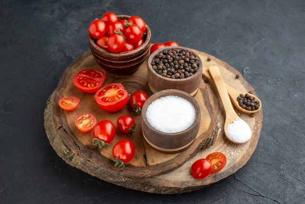 Close up shot of fresh tomatoes and spices on wooden board on black surface with free space